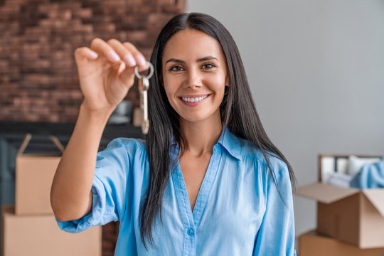 Happy woman apartment owner or renter with keys looking at camera