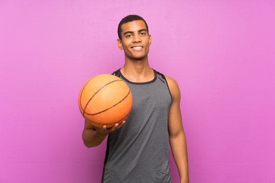 Young sport man with ball of basketball over isolated purple wall smiling a lot