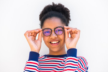Close up of young african american girl holding eyeglasses and smiling by white background