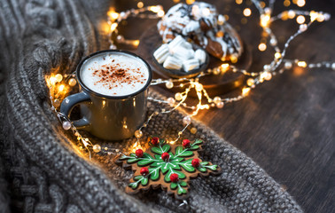 Tuinposter Cup of coffee with cinnamon. Christmas background with lights, warm knitted scarf.
