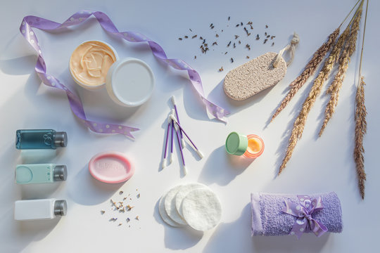 Natural cosmetic and bath products on white background in sunlight rays. Dry lavender flowers and wild cereal grass. Concept of face and body skincare at home, spa or wellness center