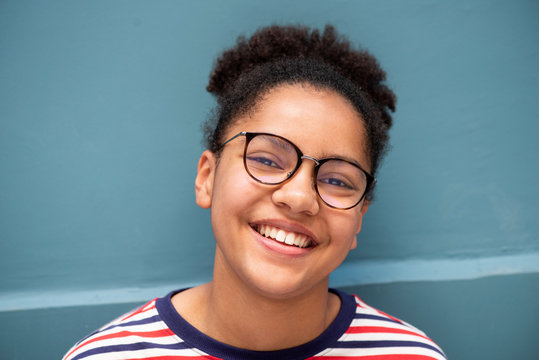 Close up of smiling young mixed race girl with glasses against blue wall