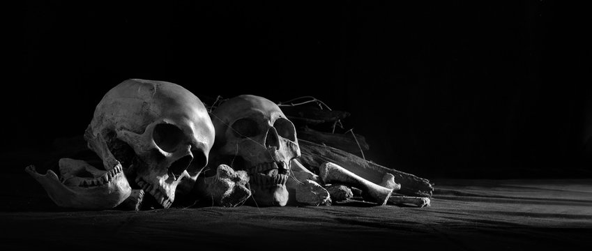 Skulls with pile bone front dark background and on black cloth floor