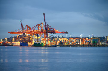 International cargo ship with containers cargo illumination and gantry cranes at port Wall mural