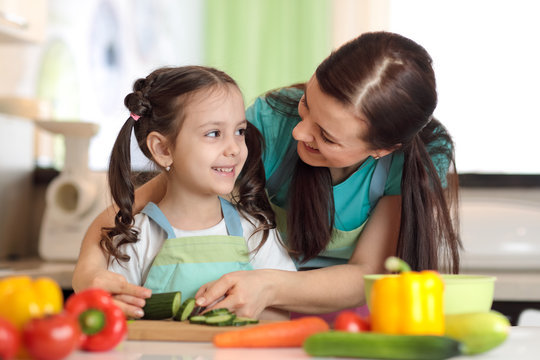 Happy mother and her kid daughter enjoy making healthy meal together at their kitchen