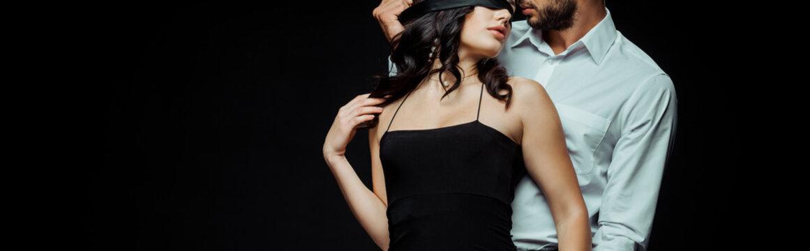 panoramic shot of bearded man near blindfolded girlfriend isolated on black