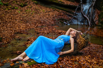 A beautiful woman in blue dress near a waterfall in autumn day