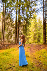 Beautiful woman in blue dress in the forest in autumn day