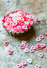 Shapes of pink heart sugar on rustic background