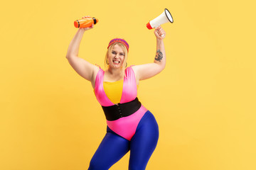 Young caucasian plus size female model's training on yellow background. Copyspace. Concept of sport, healthy lifestyle, body positive, fashion, style. Stylish woman with bottle and mouthpeace.