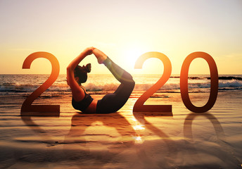 Poster de jardin Ecole de Yoga Happy new year card 2020. Silhouette of healthy girl doing Yoga Bow pose on tropical beach with sunset sky background, woman practicing yoga as a part of the Number 2020 sign.