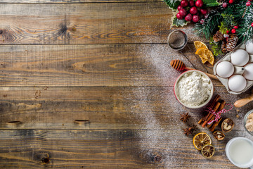 Christmas baking background. Ingredients for cooking xmas baking. Flour, eggs, sugar, berry, spices on wooden background with christmas decor,. Top view copy space.
