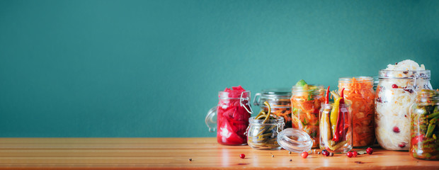 Photo sur Aluminium Nourriture Probiotics food background. Korean carrot, kimchi, beetroot, sauerkraut, pickled cucumbers in glass jars. Winter fermented and canning food concept. Banner with copy space