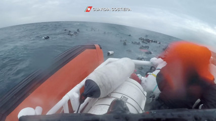 Migrants are seen floating in the Mediterranean sea after their boat capsized, during a rescue operation by the Italian coast guard