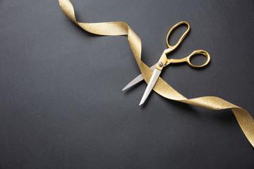 Grand opening. Gold scissors cutting gold satin ribbon, black background