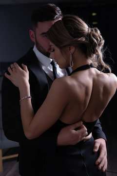 The man unbuttons the dress modestly embracing his girl