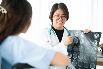 Doctor or physician take care of patient at the hospital.Beautiful female medical doctor is talking to patient reviewing brain X-ray picture,radiographic image,ct scan,mri, isolated hospital clinic.