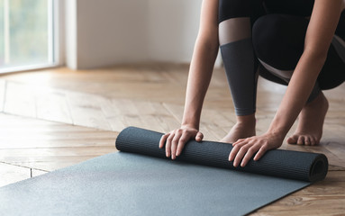 Cropped photo of girl rolling sport mat at studio