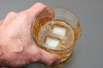 Male hand taking a glass of whiskey