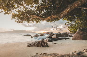 Amazing Travel landscape during Sunset on La digue with beautiful view on a hammock with iconic rocks of seychelles, travel lust concept