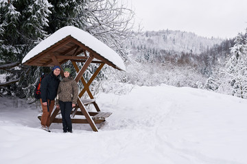Fototapete - Content couple standing under a shelter while hiking in winter