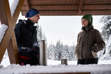 Fototapete - Couple drinking coffee during a break from their winter hike