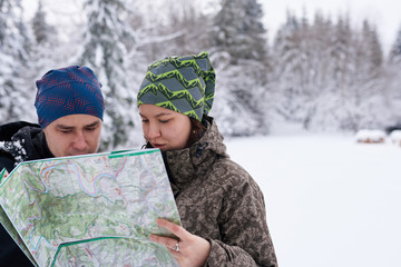 Fototapete - Couple reading a map while hiking in winter