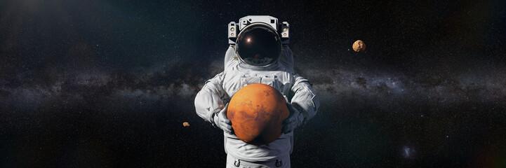 Fototapeta astronaut holding Mars, Phobos and Deimos orbiting the planet obraz
