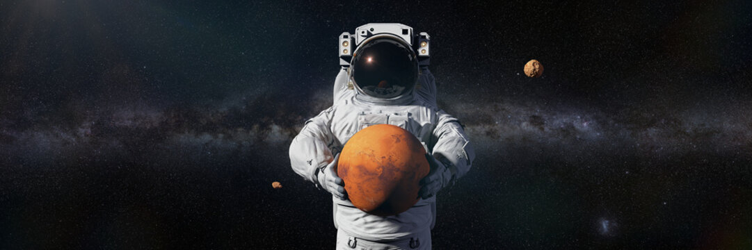 astronaut holding Mars, Phobos and Deimos orbiting the planet