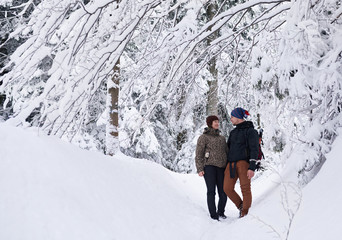 Fototapete - Content couple standing in a snowy forest while out hiking