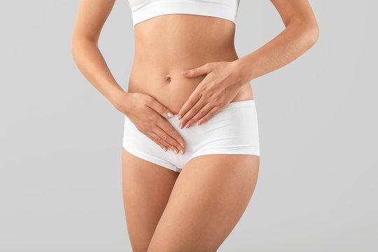 Young woman on grey background, closeup. Gynecology concept