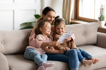 Happy young mother read book embrace little children daughters