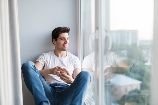 Handsome man sitting at window sill and drinking morning coffee