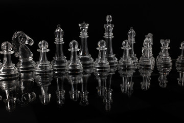 Transparent methacrylate chess pieces, front view placed on a reflective black surface