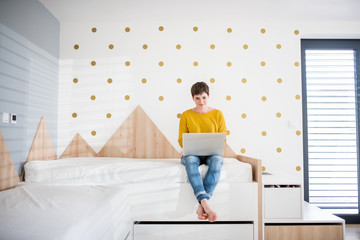 Young woman with laptop sitting on bed in bedroom indoors at home.