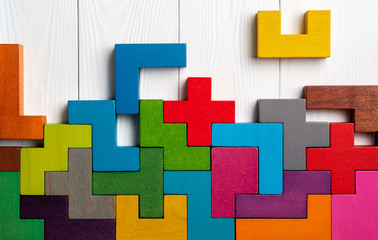 Top view on colorful wooden blocks folding on white wooden background