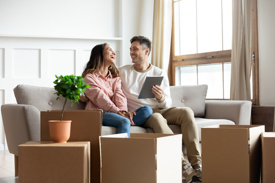 Smiling couple talking using tablet computer on moving relocation day