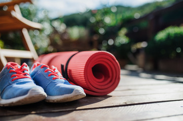 Exercise mat and trainers outdoors on a terrace in summer. Fotomurales