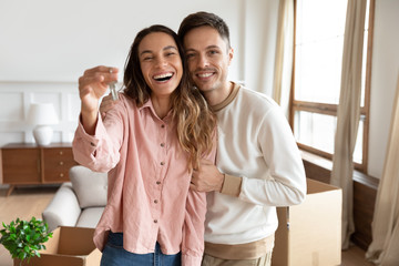 Happy couple holding key to new home on moving day