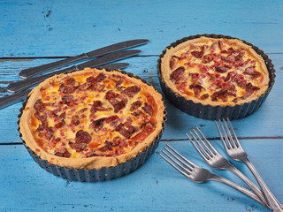 Homemade quiche with chanterelles and bacon, on blue background