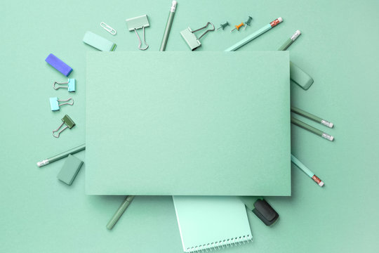 Blank paper sheet and stationery on turquoise background