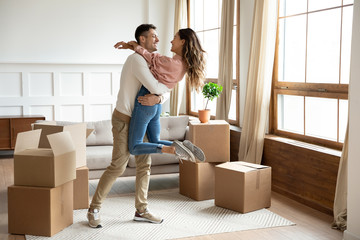 Happy husband lifting excited wife celebrating moving day with boxes