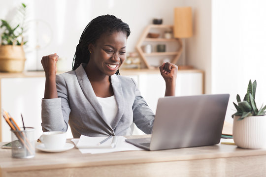 Excited Afro Businesswoman Celebrating Success At Workplace In Modern Office