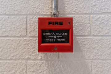 Fire alarm switch on white brick wall, break glass press here, safty system concept, Copyspace and background.