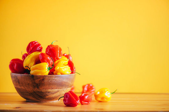 Colorful scotch bonnet chili peppers in wooden bowl over orange background. Copy space.