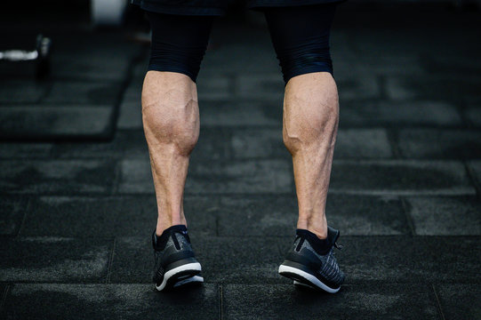 trained legs with muscular calves in sneakers in training gym during hard fitness and crossfit workout