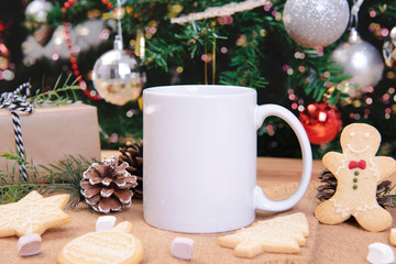 White ceramic coffee cup and christmas decoration on woon table background. mockup for creative...