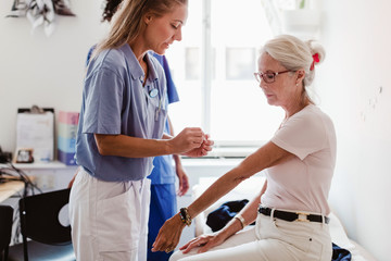 Doctor applying bandage on hand of senior woman in medical examination room