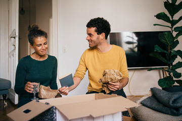 Smiling boyfriend showing novel to girlfriend while removing glasses from box in living room at new home