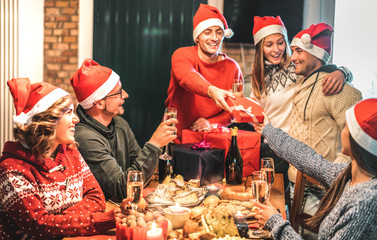 Friends group wearing santa hat giving each other Christmas presents - Champagne wine toast at home...